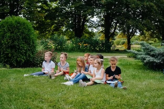 先生は屋外公園で子供たちのクラスを教えています