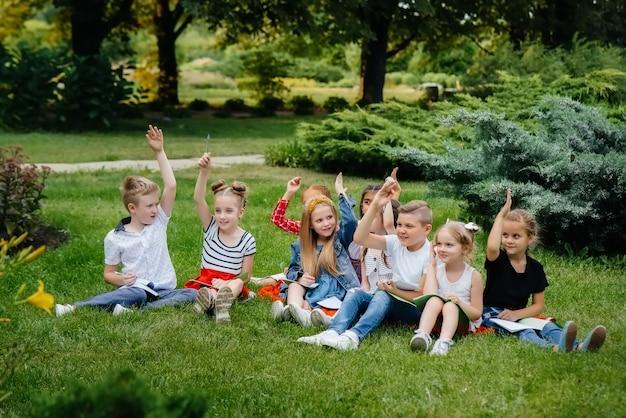 Учитель ведет класс детей в открытом парке