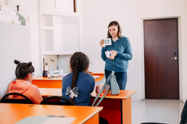 Teacher teaches children in classroom showind small board