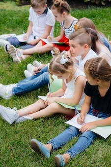 A teacher teaches a class of children in an outdoor park. back to school, learning during the pandemic.