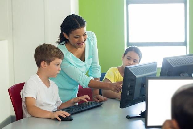 Teacher teaching computer to children