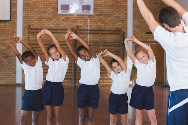 Teacher teaching exercise to school kids in basketball court