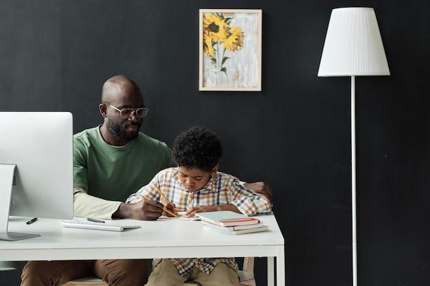 家で小さな男の子を教える先生