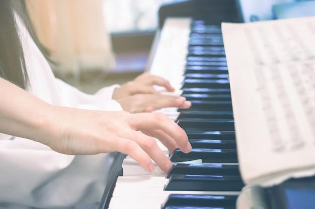 Учитель учит маленькую девочку игре на пианино концепция изучения музыки и творческого хобби