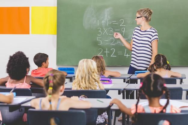 教室で学校の子供たちに数学を教える先生