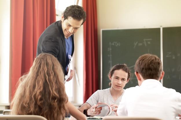 Преподаватель преподаёт или воспитывает на доске класс в школе