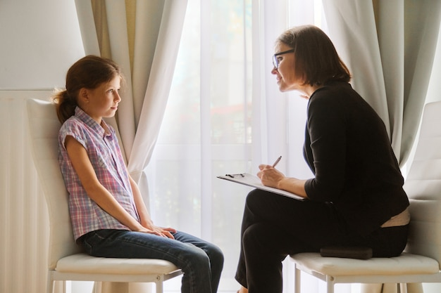 Teacher teaching and talking to a girl child, private individual lesson