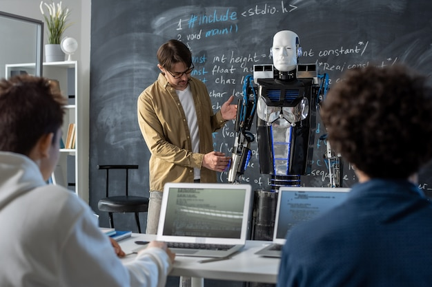 Teacher of technical university standing by automation robot by blackboard while presenting innovation to group of students at seminar