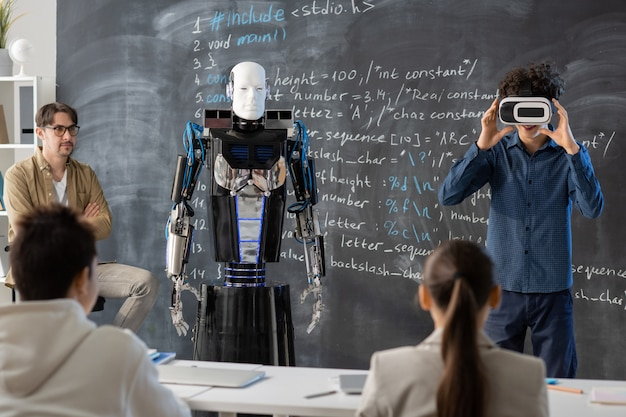 Teacher and teenage classmates looking at one of students with vr headset making presentation of robot against blackboard at lesson