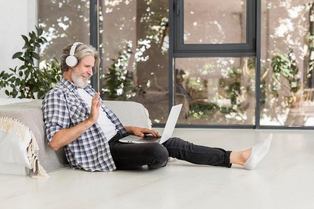 Insegnante che per mezzo del computer portatile che si siede sul pavimento