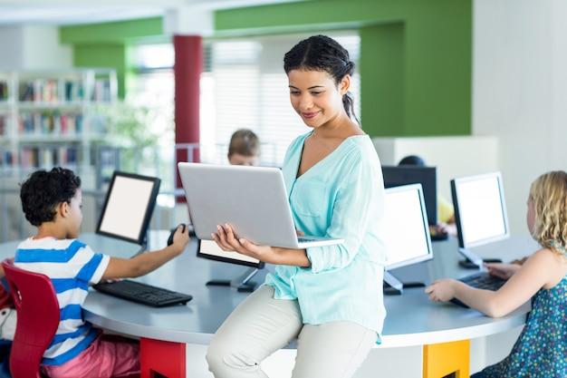 Teacher using laptop with computer class