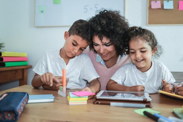 Учитель с помощью планшета с детьми в детском саду - внимание на лицо девушки