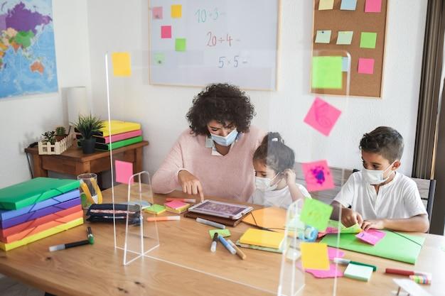 Воспитатель с помощью планшета с детьми в детском саду в защитных масках - внимание на руку женщины