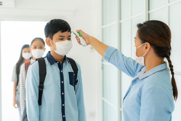 Teacher using thermometer temperature screening student for fever against the spread of covid-19