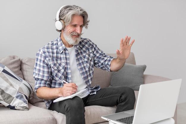 Учитель машет рукой на ноутбуке