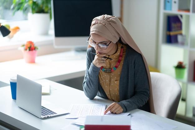 眼鏡をかけている先生。眼鏡をかけているイスラム教徒の先生がレッスンの準備をしながら思慮深く感じています