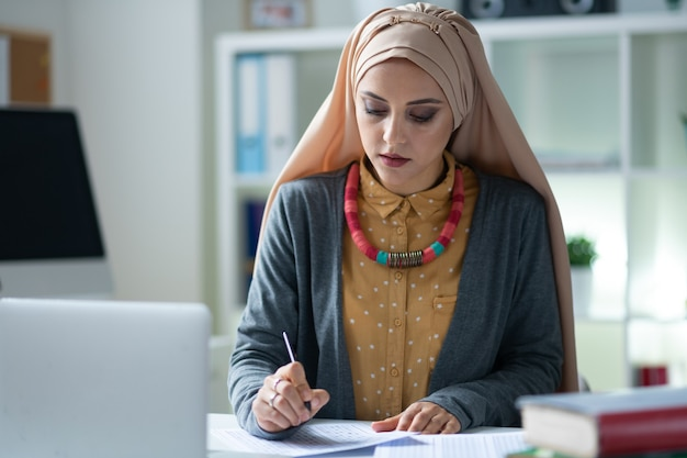 ヒジャーブを着ている先生。テストの修正に忙しいヒジャーブを身に着けているスタイリッシュなイスラム教徒の教師