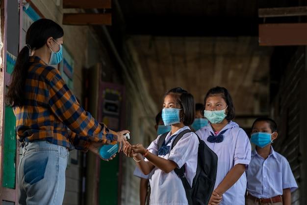 Учитель носит защитную маску для защиты от covid-19 и обрабатывает руки учеников антисептиком в классе, начальной школе, обучении и людях.