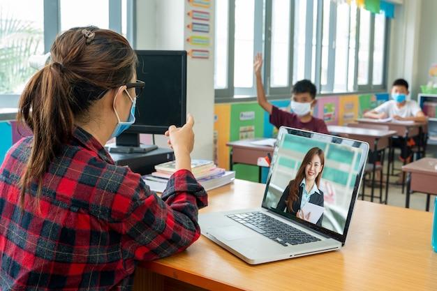 Учитель в защитной маске для защиты от covid-19 обучает школьников, сидящих в классе, онлайн, начальной школе, концепции обучения и людей.
