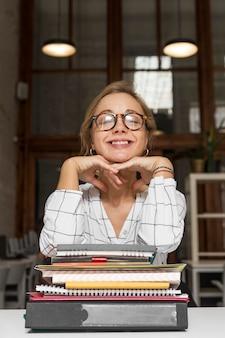 Учитель с локтем на стопке на книгах