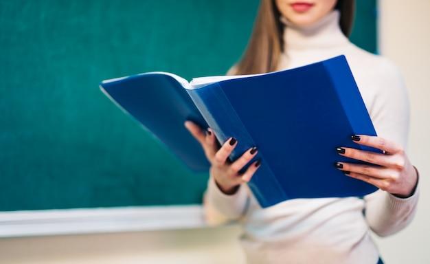A teacher with a folder in the classroom