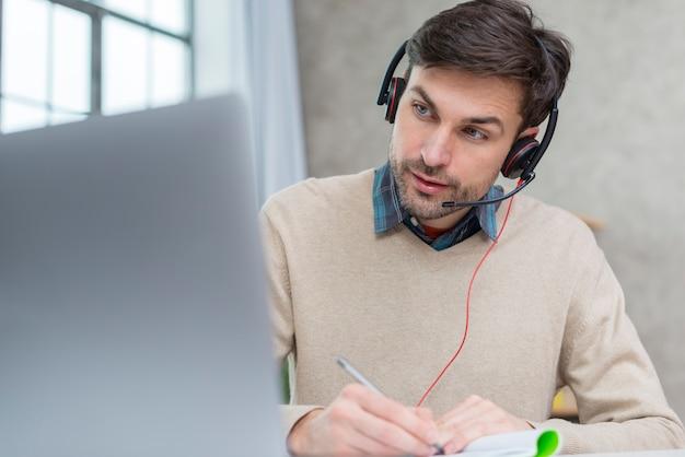 Учитель в наушниках проводит онлайн-встречу