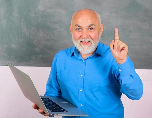 교실에서 노트북을 들고 손가락을 위로 가리키는 교사 학생들에게 수업을 하는 교수