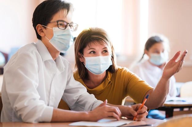 Insegnante con maschera che spiega agli studenti