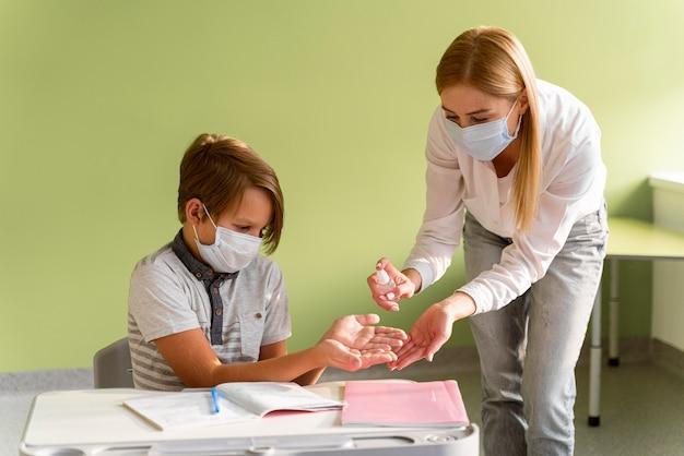 Insegnante con mascherina medica che disinfetta le mani del bambino in classe