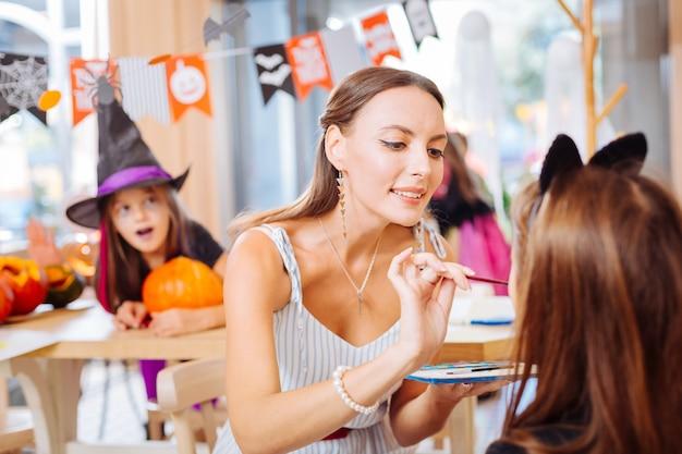 絵筆を持った先生。面白いハロウィーンのお祝いのために顔をペイントしながら絵筆を持っている幼稚園の先生