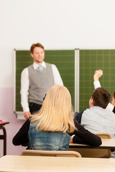 Teacher with pupil in school teaching