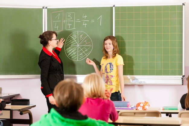 Teacher with pupil in school teaching