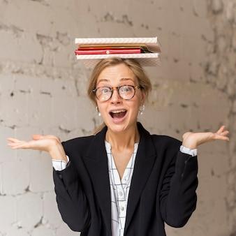 頭の上の本のスタックを持つ教師
