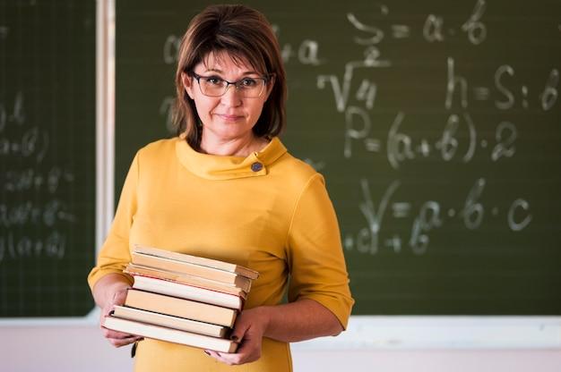 本のスタックを持つ教師
