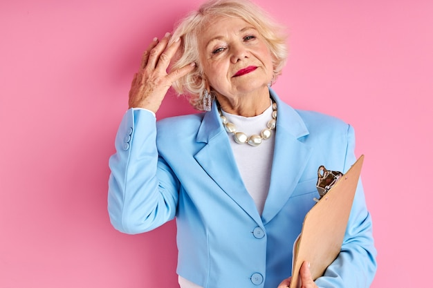 Teacher with tablet isolated over pink space, wearing elegant formal blue blouse jacket, elderly female confidently looking at camera