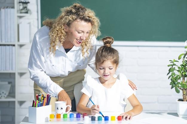교실에서 어린 학교 아이와 교사입니다. 엄마와 딸 학습.