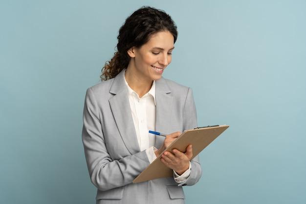 Женщина-учитель носит серый пиджак и пишет, делает заметки в документе, держит папку в изолированной руке