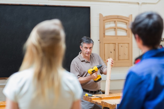 Teacher of a woodwork class teaching two students