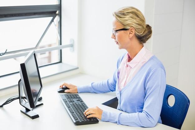 Teacher working on computer in classroom