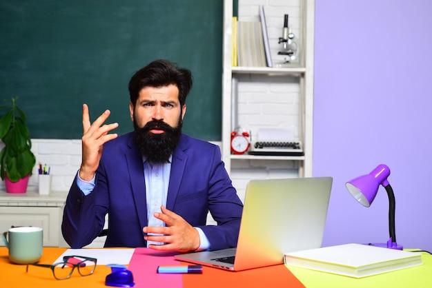 Teacher works with laptop in classroom hard work back to school online test school education