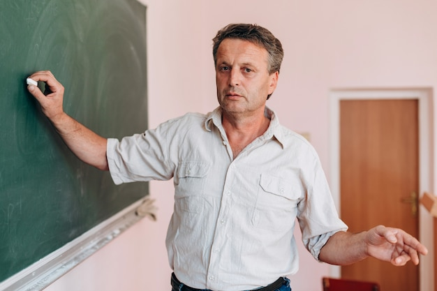 Teacher write on the blackboard and explain a lesson.