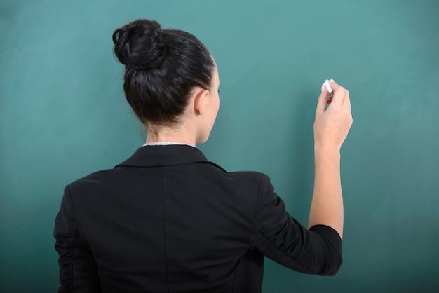 The teacher writes on the green blackboard