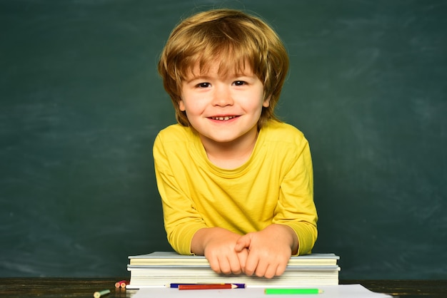 Teachers day cute little preschool kid boy in a classroom happy smiling pupils drawing at the desk s...