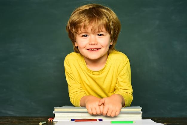 先生の日かわいい幼稚園児の男の子が教室で幸せな笑顔の生徒が机に絵を描いています...