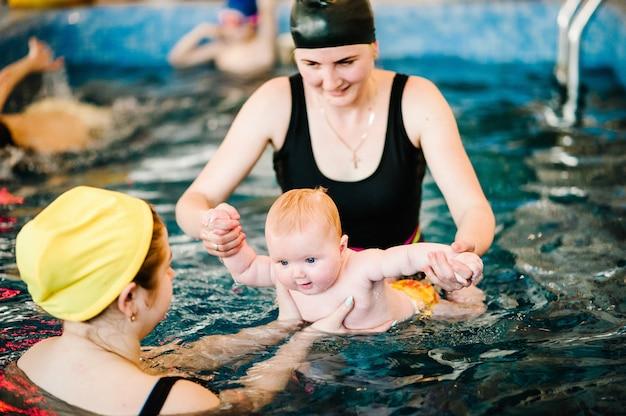 Учит маленького ребенка плавать. наслаждайтесь первым днем купания в воде.