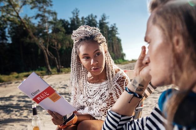 中国語を教える。彼女のブロンドの髪のボーイフレンドを中国人に教える白いドレッドヘアを持つアフリカ系アメリカ人の女性
