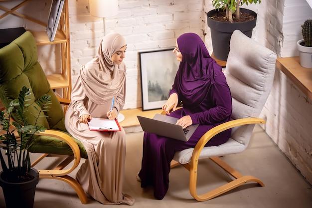 가르치는. 수업 중에 집에 있는 행복하고 젊은 두 명의 이슬람 여성, 안락의자, 온라인 교육. 문화, 전통, 현대인. 기기 화면을 보거나 쇼핑을 하거나 이야기를 합니다.
