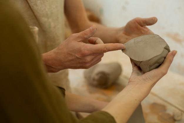 新入生を教える。マスターは新鮮な粘土のカットピースを指して、プロパティと使用法について話します
