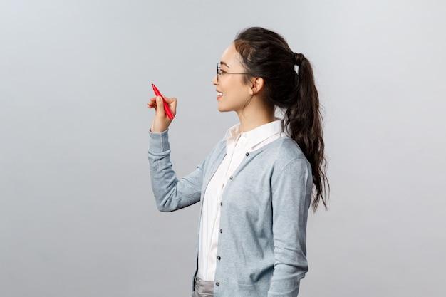 Обучение, онлайн-образование и концепция образа жизни. умная молодая учительница записывает на доске, объясняет упражнение студентам, занимающимся на расстоянии, улыбается, держа ручку, и смотрит налево
