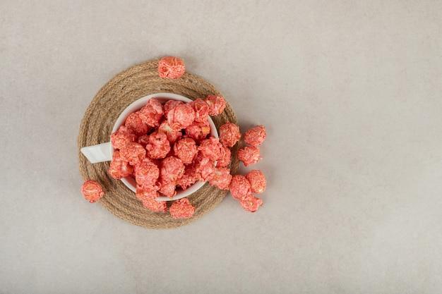 Tazza da tè su un sottopentola che scorre con popcorn rosso su marmo.